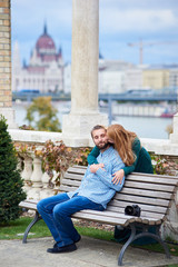 Guy is sitting on the bench, the girl is standing behind and bent to kiss him against the background of European architecture with a blurred background. On the bench next to the guy is a camera