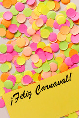 Carnaval party background concept. Space for text, copyspace. Paper in spanish: Feliz Carnaval. Confetti.