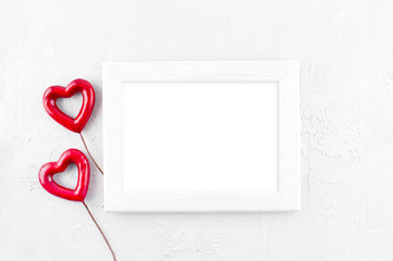 Empty wooden frame and two red hearts