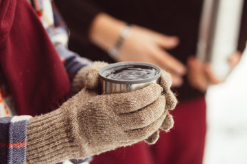 A cup of tea from a thermos on winter picnic in the woods. Woman hand's in a warm gloves