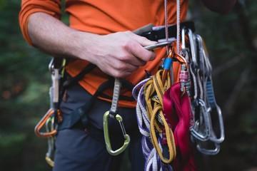 Hiker adjusting the carabiner on rope