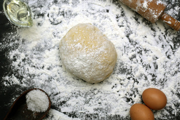 Ingredients for the preparation of dough. Fresh eggs, salt, rolling pin, and olive oil on a black background