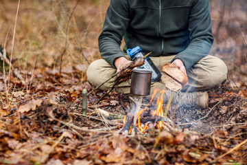 Hands of a hunter breaking and frying bread. bushcraft concept
