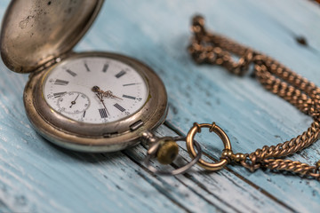 Vintage silver pocket watch on wooden table.Selective Focus