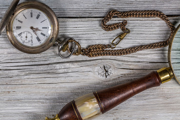 Vintage pocket-watch and Magnifying Glass on the rustic desk