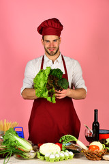 Cook works in kitchen with vegetables and tools.