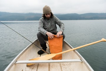Man in boat opening his bag