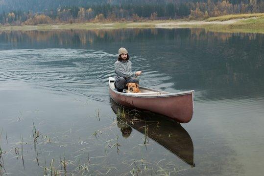 Man oaring canoe in river