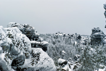 landscape with giant frozen stone cliffs-buttes of a winter forest on a highland plateau