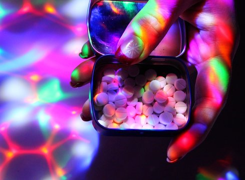 A young woman with nice nails offers ecstasy on a disco.