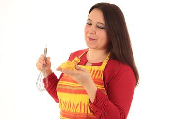 Frau in Kochschürze mit Nudeln und Schneebesen