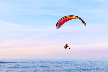 Motor Paraglider flying over the surface of the water in the evening