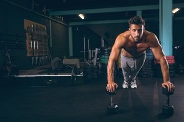 Portrait of muscular man doing push-up with dumbbells