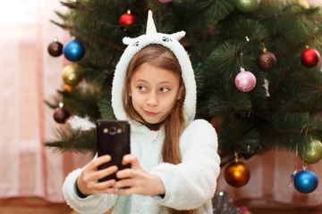 Happy little girl taking a selfie by a decorated Xmas tree on Christmas eve