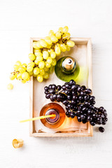 Image from above of wooden tray with green and black grapes, two bottles of juice