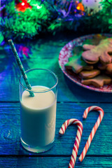 Image of Christmas cookies, glass of milk, caramel sticks, spruce branches with burning garland