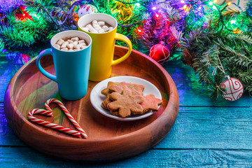 Picture of Christmas cookies, two mugs with cocoa with marshmallow, caramel sticks, branches of spruce