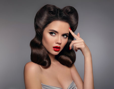 Pin up girl with red lips makeup and retro curls hair style. Retro woman looking to the side holds a finger near the head. Expressive facial expressions. High fashion photo.