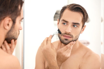 Young man shaving and looking in mirror in bathroom