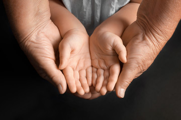 Hands of elderly man and baby on dark background
