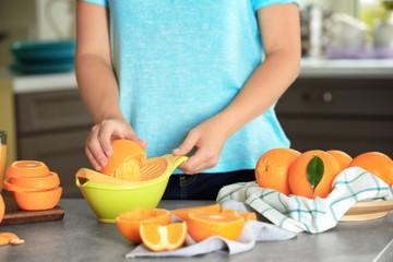 Woman making orange juice in kitchen