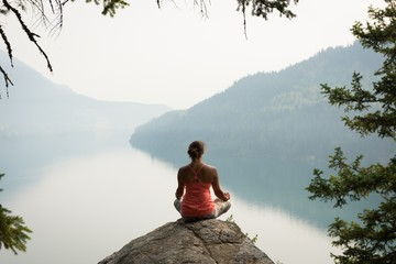 Fit woman sitting in meditating posture on the edge of a rock