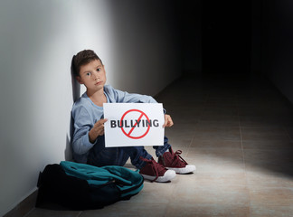 "Upset little boy sitting in hallway with crossed word ""Bullying"" on sign"
