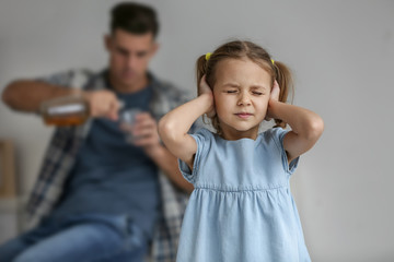 Little girl covering ears and her father drinking alcohol on background