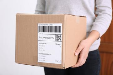 Woman holding parcel box near door, closeup
