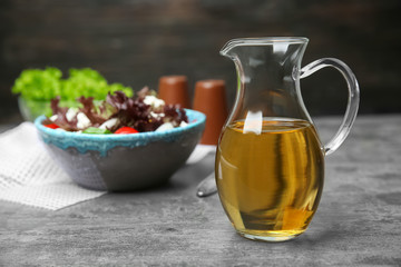 Jug with tasty apple vinegar on table