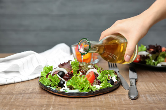Woman adding tasty apple vinegar to salad with vegetables on table