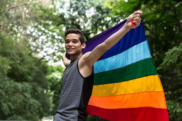 Gay Boy Waving Rainbow Flag in the Park