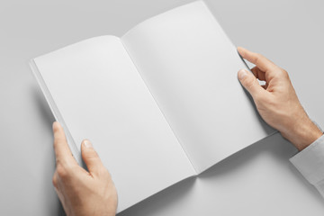 Man holding book with blank pages on white background. Mock up for design