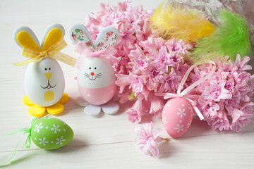 Easter background with pink hyacinths, decorative eggs and toy rabbits