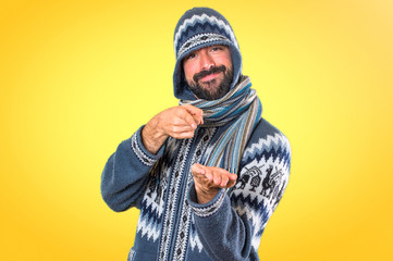 Man with winter clothes holding something on colorful background