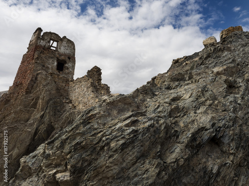 The Ruins Of An Old Fortress On Top Of A Rock Cliff Under A