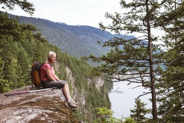 Mature woman relaxing on rock and looking at view
