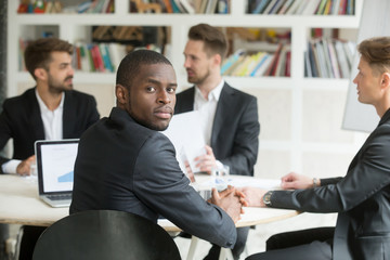 Confident african american businessman looking at camera sitting at group corporate team meeting, black company leader in suit posing with partners at background, executive manager headshot portrait
