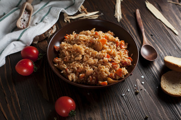 pilau in a brown ceramic dish, a kitchen towel, cherry tomatoes and a basket with spikelets of wheat, bread and a wooden spoon on a dark wooden table