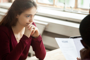 Nervous stressed female applicant waiting for result at hiring negotiations, insecure woman candidate feeling worried while hr managers read discuss her cv resume, bad failed job interview concept