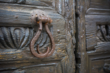 Horizontal View of a Close Up Of An Old Steel Clapper On An Ancient Wooden Decorated Door