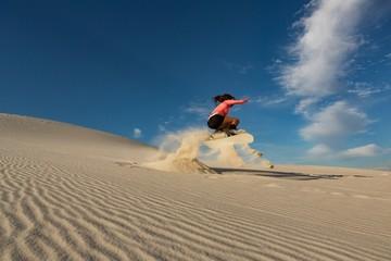 Woman sandboarding on sand dune