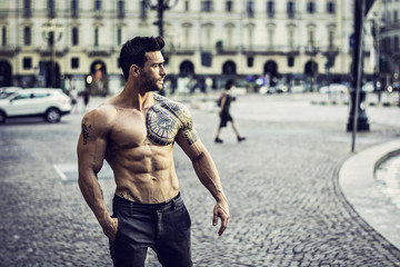 Handsome muscular man with tattoo posing in European city centre.