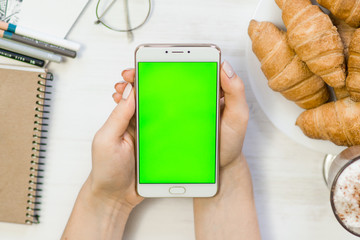 smartphone in the hands of a green screen in a cafe, smart phone with chroma key green screen on white background, new technology concept top view