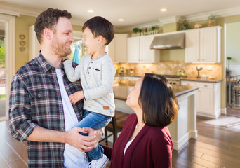 Young Mixed Race Caucasian and Chinese Family Inside Custom Kitchen.