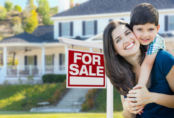Young Mother and Son In Front of For Sale Real Estate Sign and House.