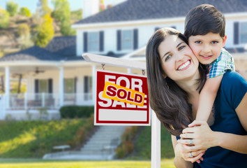 Young Mother and Son In Front of Sold For Sale Real Estate Sign and House.