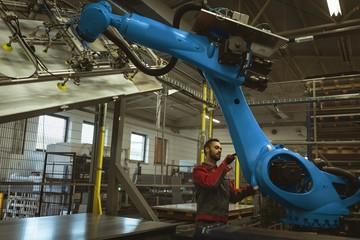 Male worker checking robotic machine