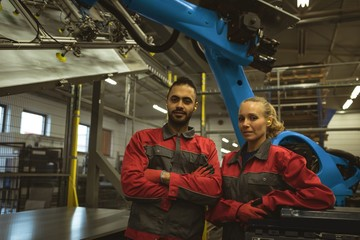 Male and female worker standing together with arms crossed in