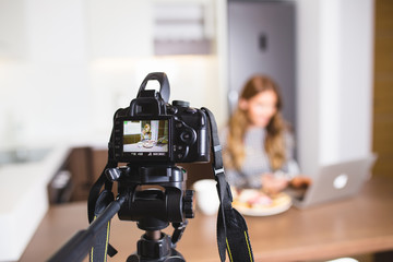 Young female vlogger recording content for her video blog. Fashion and food concept.